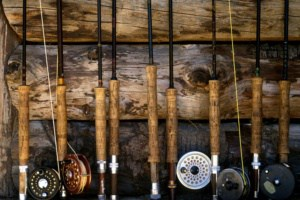 A row of fly fishing poles up along a wall.