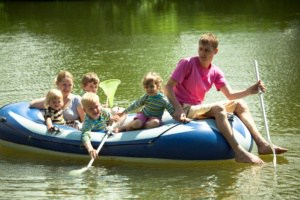 Children and adults float on an inflatable boat and fish a net.